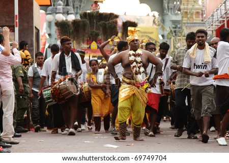 BATU CAVES, MALAYSIA - JANUARY 19:A man in trance walks ahead of a Kavadi procession during the Hindu festival of Thaipusam on January 19, 2011 in Batu Caves, Malaysia. - stock photo