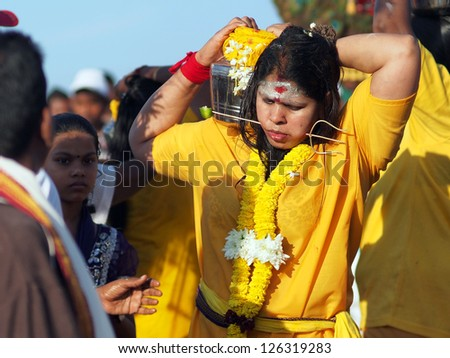 BATU CAVES, MALAYSIA - JANUARY 27: An unidentified woman carries a pot of milk during the celebration of Thaipusam in Batu Caves, Malaysia on January 27, 2013.