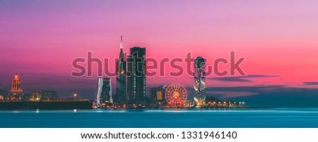 Batumi, Adjara, Georgia. Panorama of Illuminated Resort Town at Sunset. Black Sea Technological University, Ferris Wheel and Alphabet Tower