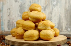 Baursaki is a traditional pastry of national oriental cuisine. On a wooden plate, on a gray textured background