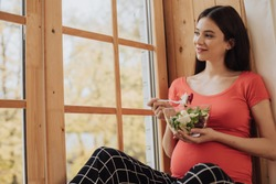 Bautiful picture of nice young pregnant woman sitting at window and eat salad from glass bowl. Look at windown and smile. Relaxed calm and peaceful brunette. Maternity time. Future single mom