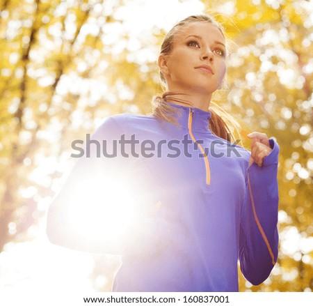 Bautiful running woman jogging in autumn nature