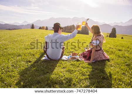 Bavarian Couple Cheering With A Beer Mug. Bavarian Couple in traditional german clothes drinking beer in Bavaria, Germany. Cheering Beer Mug Bavaria Allgau