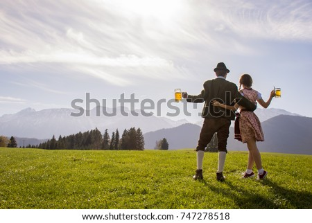 Bavarian couple in traditional clothes holding beer mug in hand, Bavaria Germany. Bavarian couple celebrating Oktoberfest from Munich Germany Bavaria