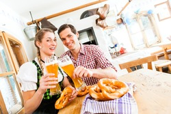 Bavarian couple wearing traditional dress, flirting and  drinking beer in restaurant