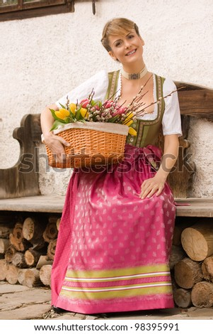 Bavarian girl sitting on a bench in dress and bouquet of Easter basket /Young girl with Easter bouquet Bavarian