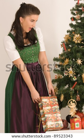 Bavarian girl with Christmas parcels before a table with Christmas gifts /Bavarian Girl with Christmas present