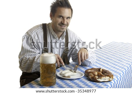 Bavarian Guy is sitting at table and having a typical Oktoberfest meal with pretzel (Brezn), veil sausage (Weisswurst), beer at beer stein (Mass). Isolated on white background.