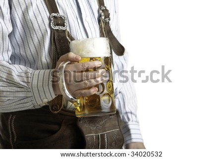 Bavarian man dressed with original leather trousers holds an Oktoberfest beer stein into the camera