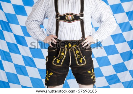 Bavarian man with black Oktoberfest leather pants (Lederhose). In background is Bavarian flag visible.