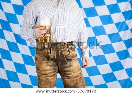Bavarian man with leather pants (Lederhose) holds Oktoberfest beer stein (Mass) . In background is Bavarian flag visible.