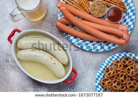 Bavarian snacks with white sausages in bouillon, viennese sausages, pretzels, sticks and beer, high angle view on a beige stone background, horizontal shot Stock photo ©