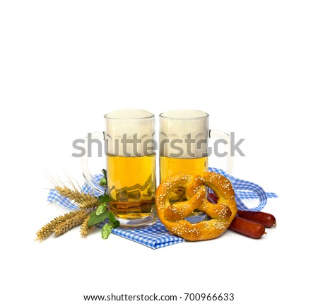 Bavarian soft salted pretzels, wheat ears, sausages, mugs of lager beer, green hop cones and blue and white doily and ribbon on white background with space for text. Oktoberfest