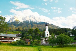 bavarian village Grainau. domed church St. Johannes, graveyard and houses with Mountains, Waxenstein and Zugspitze peaks. Wetterstein range Northern Limestone Alps Bayern Bavaria Germany Europe
