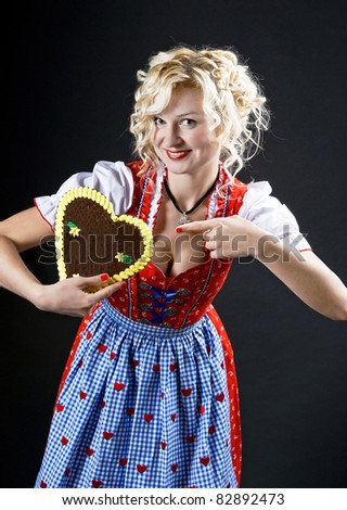 Bavarian woman in dirndl. young woman with typical Oktoberfest cookie