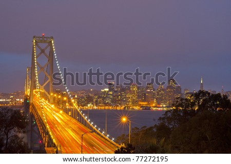 Bay Bridge at twilight with ocean in the foreground. San Francisco, USA