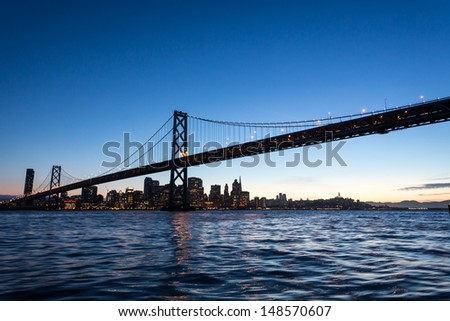 Bay Bridge spans San Francisco Harbor to Oakland on a sunny day at sunset