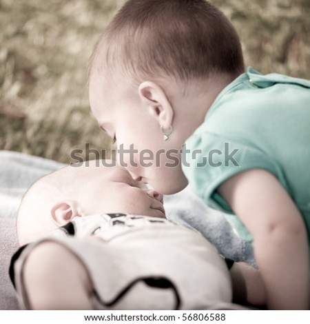 Bay girl giving a kiss to her new born baby brother - stock photo