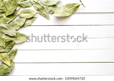 Bay leaves. Dried leaves of laurel leaf on white wooden background. Flat lay, top view, copy space