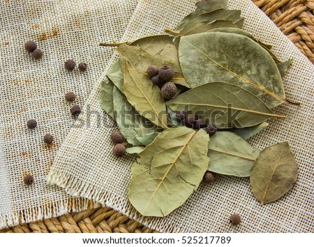 bay leaves on a straw background with pepper #525217789