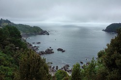Bay of water in Pacific Ocean. Hills with lush foliage. Horizon over water and overcast rainy weather with fog and dramatic sky. Chile
