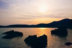 Bay vista in the dusk . Big rocks in the sea water
