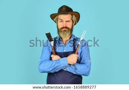 Bbq american tradition. Culinary concept. Medium rare. Bbq food. Tools roasting meat. Man in apron hold barbecue grill. Farmer promoting bbq equipment. Cooking steak. Cooking utensils. Summer picnic.