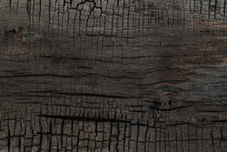 BBQ background. Burnt wooden Board texture. Burned scratched hardwood surface. Smoking wood plank background. Dark brown wooden texture empty horizontal surface, copy  space. Halloween backdrop
