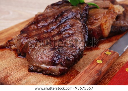 bbq beef meat fillet on wooden plate with cutlery