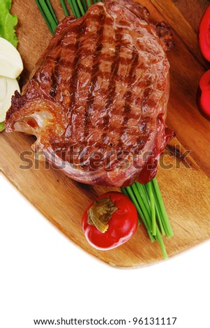 bbq : beef (pork) steak garnished with green lettuce and red chili hot pepper on wooden plate isolated over white background