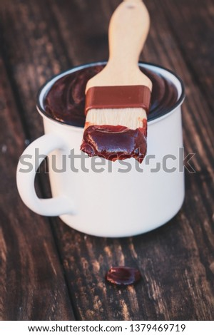 BBQ brush with barbecue sauce on the tip resting on a white cup over a rustic wood background with drop on table. Shallow depth of field with blurred background and selective focus on end of brush.