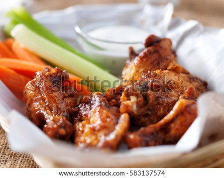 bbq buffalo chicken wings in basket, with ranch dip, carrot and celery sticks