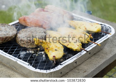 BBQ - Burgers, Satay and Sausages on a lit disposable barbecue. - stock photo