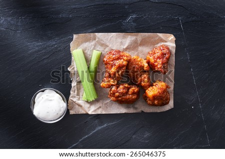 bbq chicken hot wings on parchment paper with ranch and celery