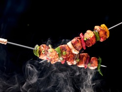 BBQ chicken skewers grilled with vegetables, on a black background