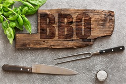 BBQ concept old board on concrete. Green basil leaves, meat knife and barbecue fork