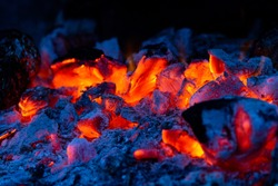 BBQ Grill pit with glowing and flaming hot charcoal briquettes, abstract background