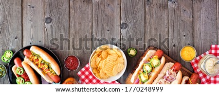 BBQ hot dog bottom border. Overhead view table scene with a dark wood banner background. Copy space.