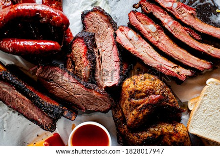 BBQ platter. Barbecue pork ribs, brisket, beef ribs and chicken served with classic bbq sides Mac n cheese, cornbread, Brussels sprouts, coleslaw & beer. Classic traditional Texas meats & side dishes. Foto stock ©