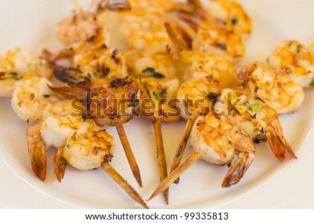 BBQ Prawns - Grilled prawn skewers on a white plate /  background. Selective focus and shallow DOF.