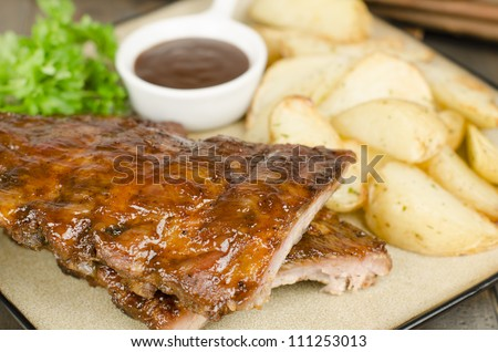 BBQ Ribs - Marinated pork ribs with potato wedges and barbeque sauce.