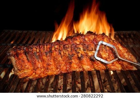 BBQ Roast Marinated Baby Back Pork Ribs Close-up On Hot Flaming Grill Background