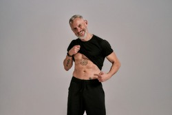Be a motivation. Smiling middle aged muscular man lifting black t shirt showing, pointing at his abs, tattoos while posing in studio over grey background. Sport and healthy lifestyle