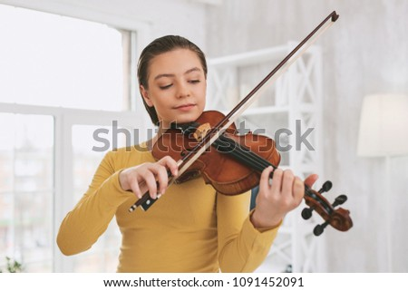 Be attentive. Pretty brunette bowing head while looking at her instrument