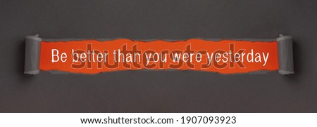 Be Better Than You Were Yesterday - text on red background appears behind torn paper ストックフォト ©