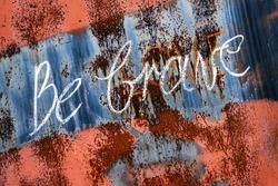 Be brave inscription on rusty surface