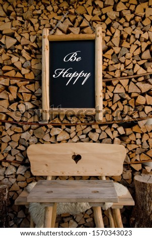 Be Happy sign in front of wooden logs and chair