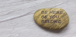 Be here, be you, belong symbol. Beautiful stone with words 'Be here, be you, belong' on beautiful white wooden background. Diversity, business, inclusion and belonging concept.