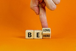 Be here belong symbol. Businessman hand turns a cube and changes words 'be here' to 'belong'. Beautiful orange background. Business, belonging and be here belong concept. Copy space.