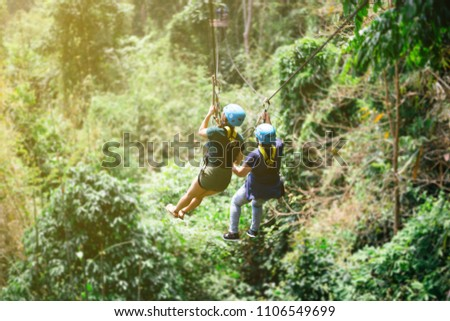 Be hide people go to Zip line in forest with sunlight,Adventure concept #1106549699
